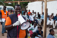 Man speaks into loudspeaker during vaccination campaign. Photo: WHO/C. Black
